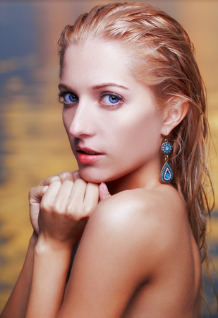 portrait of young beautiful blonde woman in ear-rings looking above her shoulder  sea on background  photo