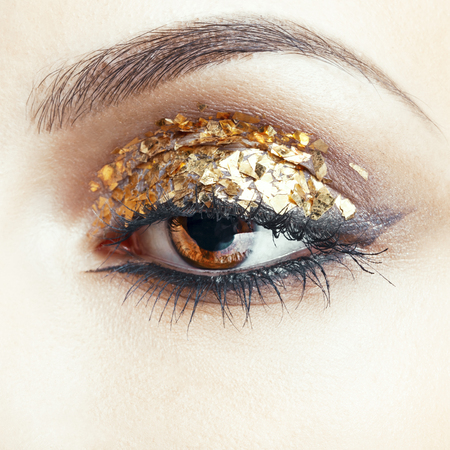Close-up shot of female face with vogue golden shining eye makeup photo