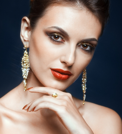 Beautiful young woman with vogue shining face makeup  photo