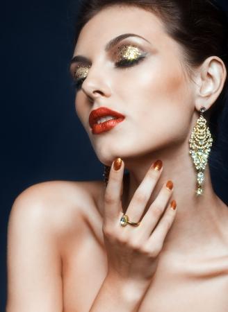Beautiful young woman with vogue shining face makeup  photo