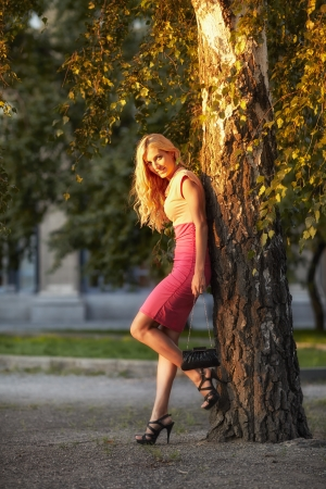 Smiling beautiful woman leaned against a birch tree. photo