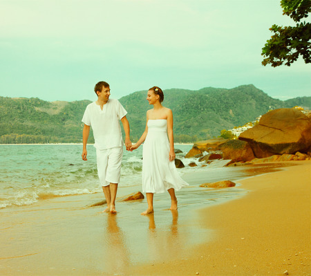 colorized vintage outdoor portrait of young romantic couple in white cotton clothes on beach of Phuket island, Thailand photo