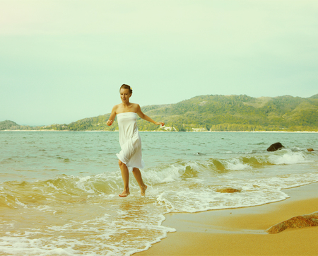colorized: Instagram colorized vintage outdoor portrait of young woman in white cotton clothes on beach of Phuket island, Thailand