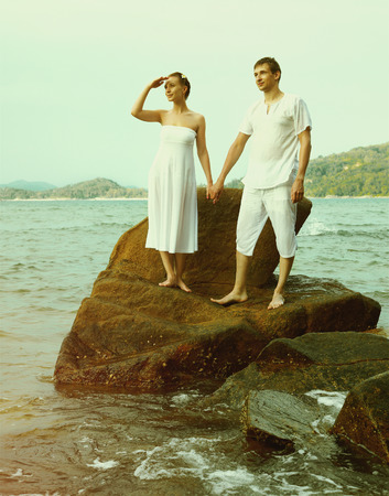 colorized: Instagram colorized vintage outdoor portrait of young romantic couple in white cotton clothes on beach of Phuket island, Thailand