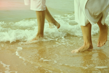 colorized: colorized vintage body part outdoor portrait of couples legs in white cotton clothes walking along coastal strip of Phuket island, Thailand