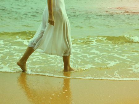 colorized: colorized vintage body part outdoor portrait of young womans legs in white cotton skirt walking along coastal strip of Phuket island, Thailand Stock Photo
