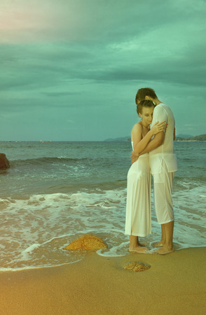colorized: colorized vintage outdoor portrait of young romantic couple in white cotton clothes on beach of Phuket island, Thailand