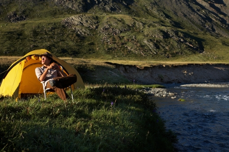 man is sitting in the chair at the camp in mountains near the stream photo
