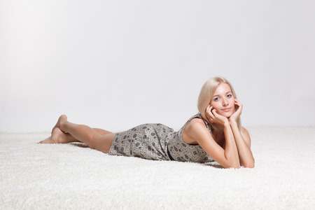 young girl barefoot: Blonde young woman on white whole-floor carpet and gray background