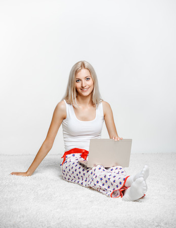 Young blonde woman in pyjamas on white whole-floor carpet browsing laptop photo