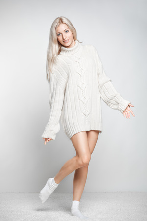 Blonde young woman dressed in long white cashmere sweater on white whole-floor carpet and gray background