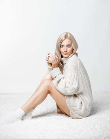 Blonde young woman dressed in large white cashmere sweater and seating on on white whole-floor carpet on gray background drinking a cap of tea photo
