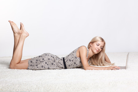Blonde young woman on white whole-floor carpet browsing laptop photo