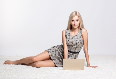 young girl barefoot: Blonde young woman sitting on white whole-floor carpet browsing laptop Stock Photo
