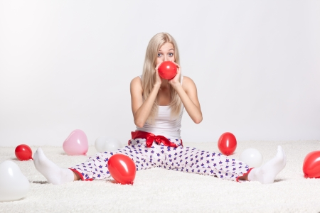 Blonde young woman sitting on white whole-floor carpet and inflating red balloon photo