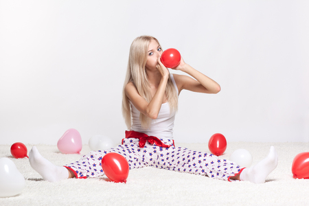 Blonde young woman sitting on white whole-floor carpet and inflating red balloon