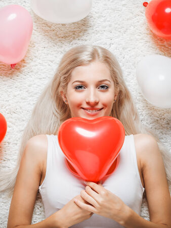 Blonde young woman on white whole-floor carpet with balloons photo