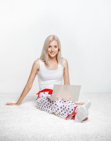 pijama: Mujer rubia joven en pijamas en blanco toda la planta portátil navegar por la alfombra
