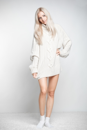 long socks: Blonde young woman dressed in long white cashmere sweater on white whole-floor carpet and gray background