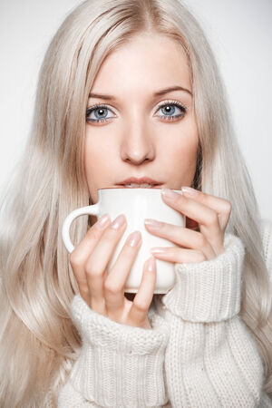 Blonde young woman dressed in large white cashmere sweater on gray background drinking a cap of tea photo