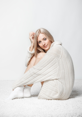 cashmere: Blonde young woman dressed in long white cashmere sweater sitting on white whole-floor carpet and gray background Stock Photo