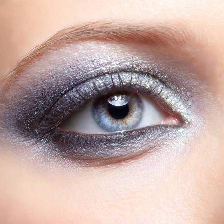 Eye of young woman with vogue shining sparkle makeup photo