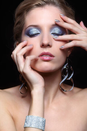 Beautiful young woman with vogue shining sparkle face makeup and closed eyes photo