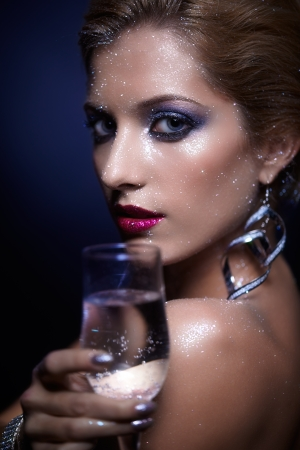 Beautiful young woman with vogue shining sparkle face makeup and glass of champagne in hand  photo
