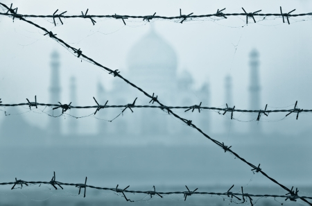 barbed wire fences: Taj Mahal in India behind barbed wire fences at early morning