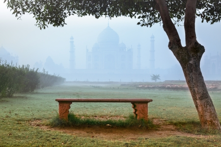 Empty bench by Taj Mahal hidden in morning fog photo