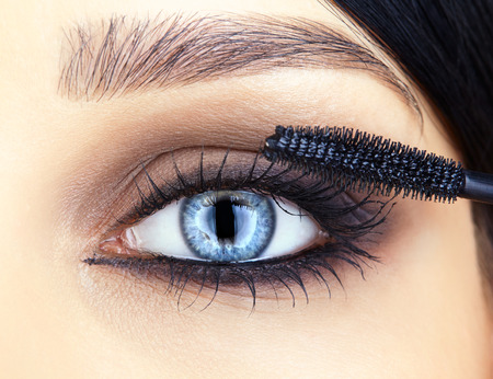 Close-up shot of woman face and makeup brush  applying mascara make-up on eye lashes photo