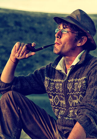 colorized: Colorized vintage outdoor portrait of tourist in hat is smoking tobacco-pipe Stock Photo