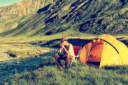 colorized: Colorized vintage outdoor portrait of tourist drinking tea at the Altai camp in mountains near the river