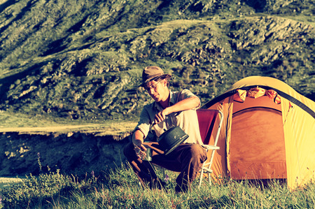 colorized: Colorized vintage outdoor portrait of tourist in Altai camp drinking tea near the stream Stock Photo