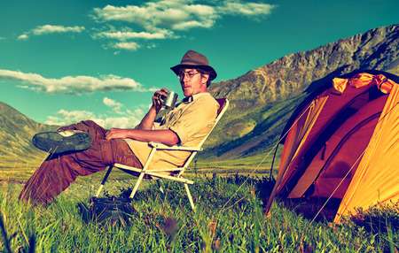 colorized: Colorized vintage outdoor portrait of tourist in Altai camp drinking tea near tent and river Stock Photo