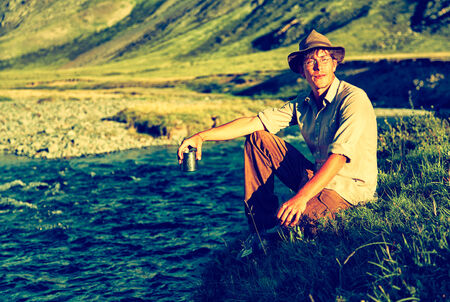 colorized: Colorized vintage outdoor portrait of tourist in Altai camp sitting near the river and drinking tea
