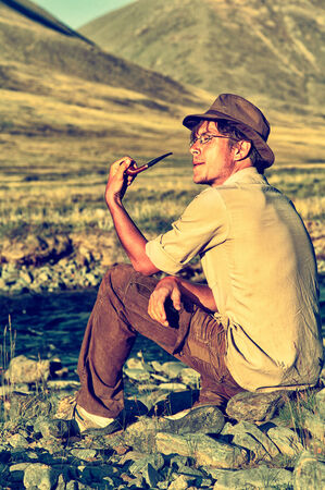 colorized: Colorized vintage outdoor portrait of tourist smoking tobacco-pipe near the stream in Altai mountains