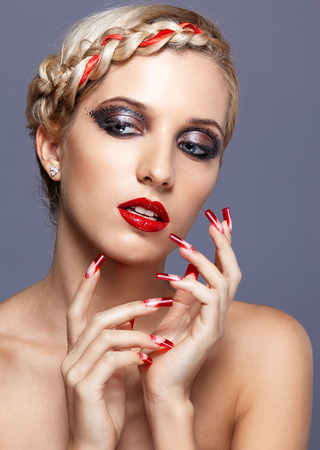 Young blonde woman with braid hairdo and red nails on gray  photo