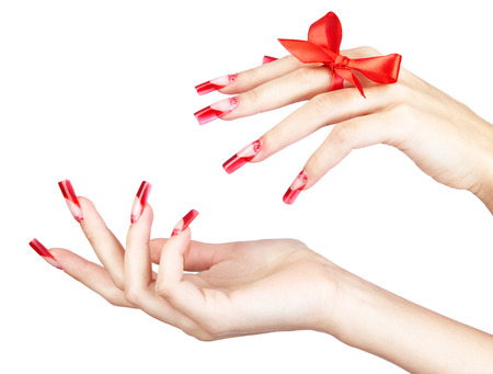 finger bow: Hands with red french acrylic nails manicure and painting with bow on finger isolated  white