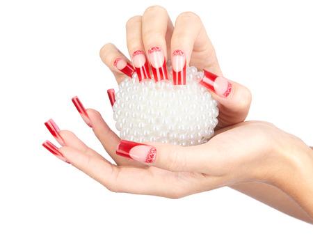 falso: Las manos con las uñas de acrílico falsas francés manicura rojos que sostiene la bola de navidad de la perla aislado en blanco