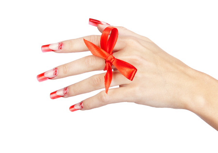 finger bow: Hand with red french acrylic nails manicure and painting with bow on finger isolated  white