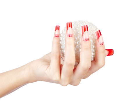 Hands with red french false acrylic nails manicure holding perl christmas ball isolated on white  photo