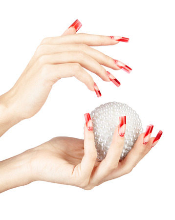 christmas manicure: Hands with red french false acrylic nails manicure holding perl christmas ball isolated on white  Stock Photo