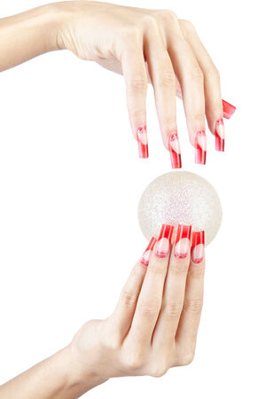 Hands with red french false acrylic nails manicure holding christmas ball isolated on white  photo