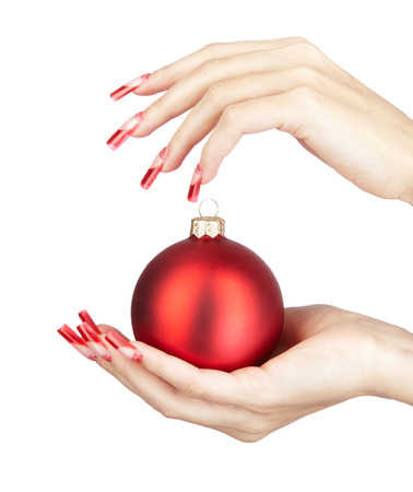 christmas manicure: Hands with red french false acrylic nails manicure holding christmas ball isolated on white