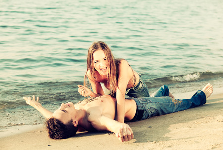 topless jeans: Colorized vintage outdoor portrait of beautiful romantic couple of topless girl and muscular guy in jeans on beach. girl drops sand on guys chest Stock Photo