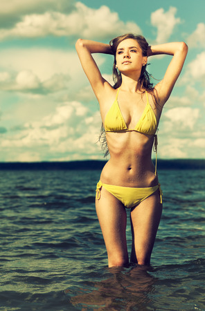 Colorized vintage outdoor portrait of Young beautiful slavonic girl in yellow bikini posing on the beach photo