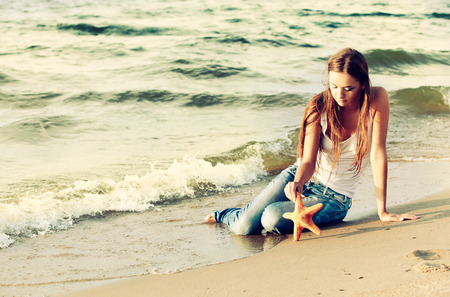 Colorized vintage outdoor portrait of outdoor portrait of beautiful girl in jeans posing on beach with asteroid photo