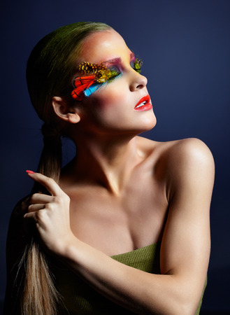 Woman with bright stylish make-up, green hair,  false fashion feather eyelashes and red manicure  photo