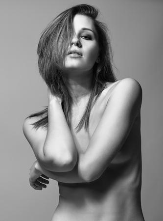 topless: Jeune jolie femme seins nus posant sur fond gris